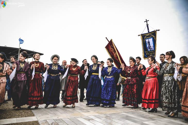 Χορευτές και τραγουδιστές συνοδευουν την παρέλαση των κωδωνοφόρων